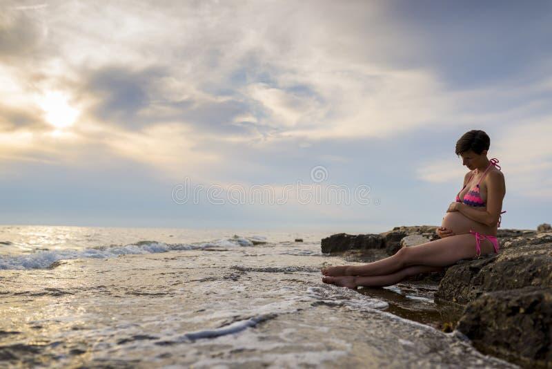 Schwangere Frau im 9. Monat der Schwangerschaft vorbei sitzend auf einem Felsen lizenzfreie stockbilder