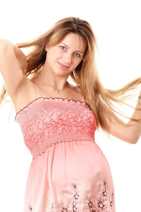 Schwangere Frau im rosafarbenen Kleid lizenzfreie stockbilder