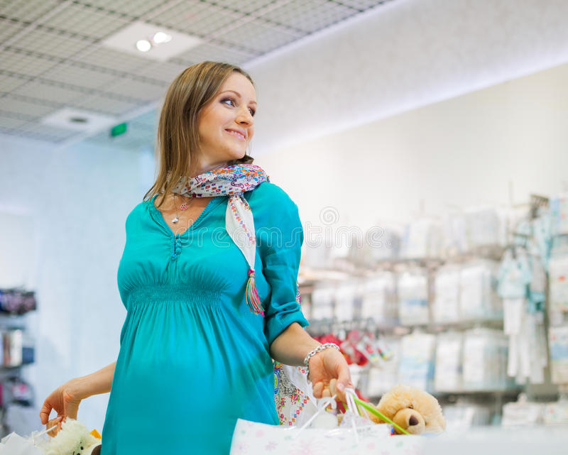 Schwangere Frau im Shopspeicher lizenzfreie stockbilder