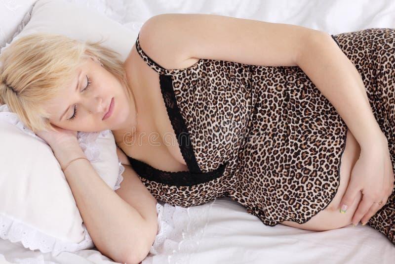 Schwangere Frau im Unterwäscheschlaf lizenzfreie stockbilder