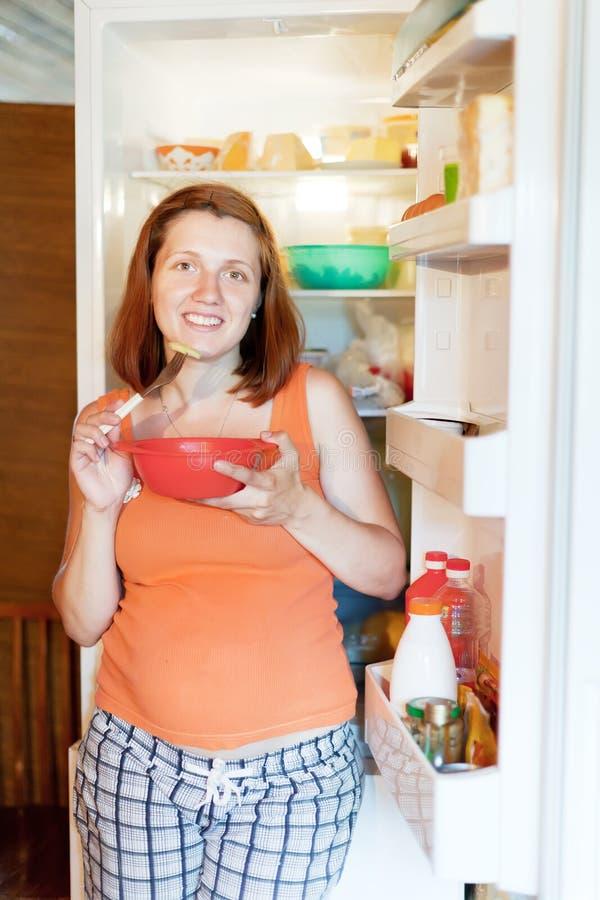 Schwangere Frau isst vom refrigerato stockbild