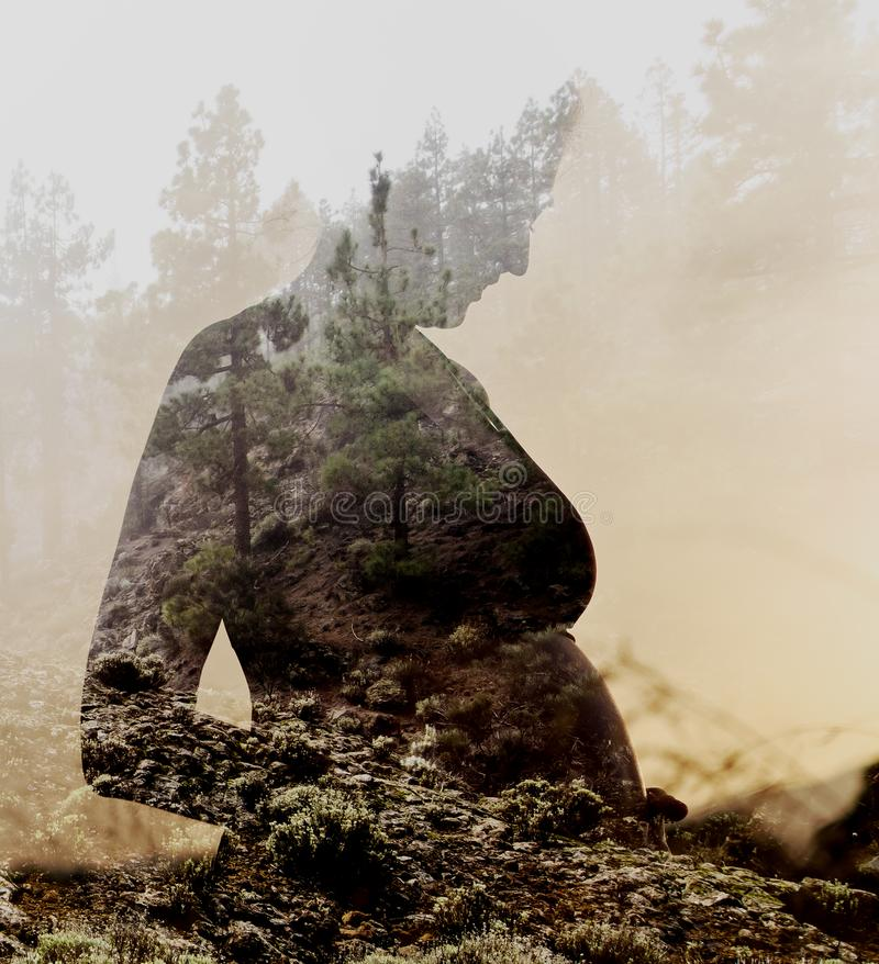 Schwangere Frau kombiniert mit Natur stockfoto