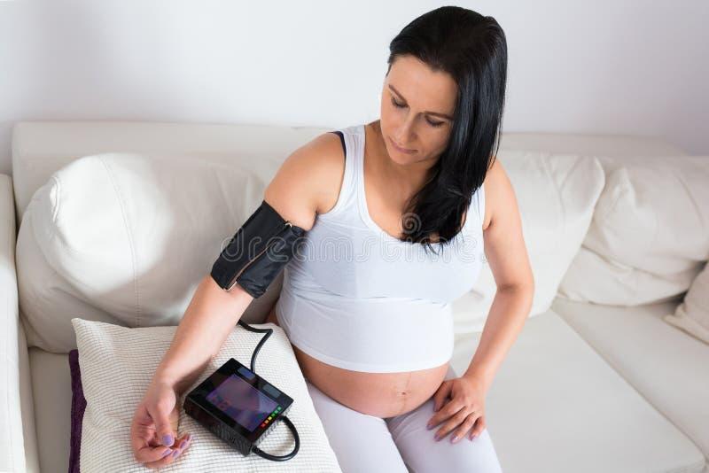 Schwangere Frau misst den Blutdruck lizenzfreies stockfoto