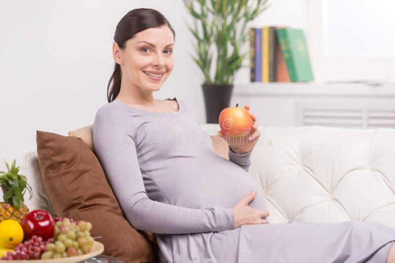 Schwangere Frau mit Apfel. stockbilder