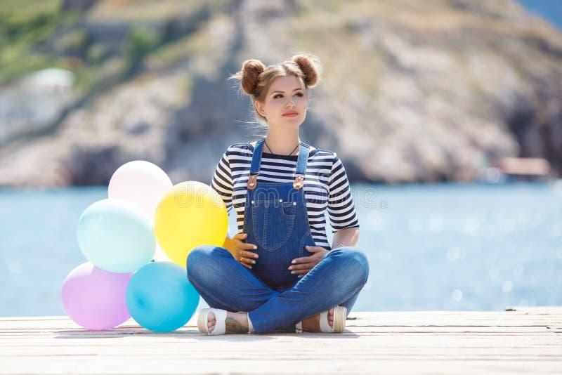 Schwangere Frau mit bunten Ballonen auf dem Strand lizenzfreies stockbild