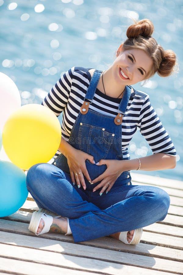 Schwangere Frau mit bunten Ballonen auf dem Strand lizenzfreie stockfotografie