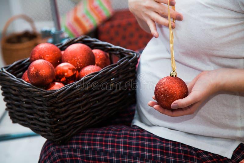 Schwangere Frau mit dem Korb voll von den roten Weihnachtsbällen stockbilder