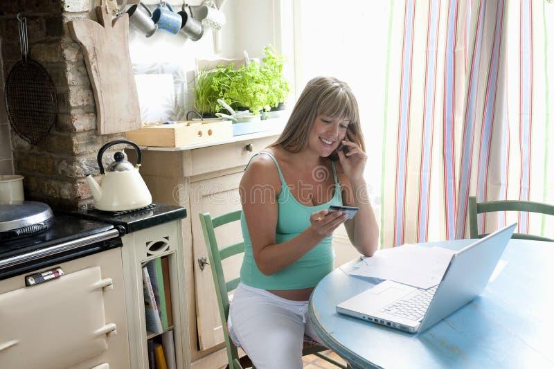 Schwangere Frau mit dem Laptop, der Kreditkarte-Kauf auf Mobiltelefon abschließt lizenzfreies stockbild