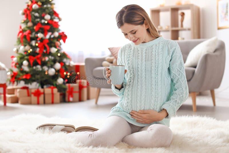 Schwangere Frau mit der Tasse Tee sitzend auf Boden im Raum verziert für Weihnachten stockfotos