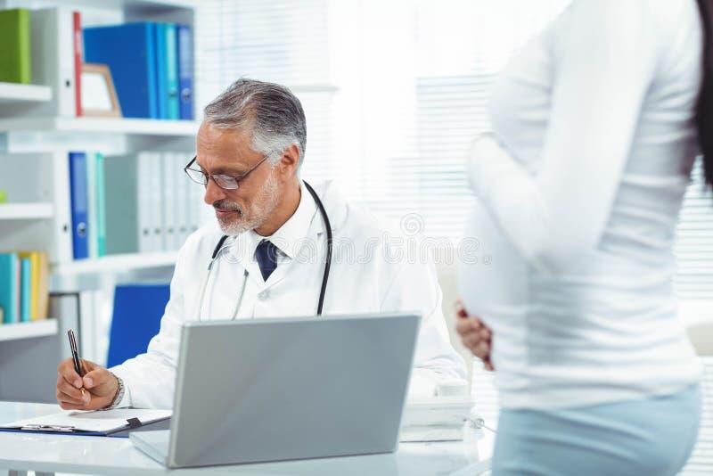Schwangere Frau mit Doktor an der Klinik lizenzfreie stockbilder