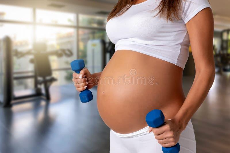 Schwangere Frau mit Dummköpfen in ihrer Hand in einer Turnhalle lizenzfreies stockfoto