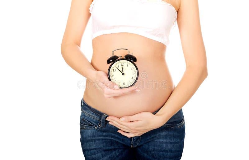 Schwangere Frau mit einer Alarmuhr lizenzfreies stockfoto