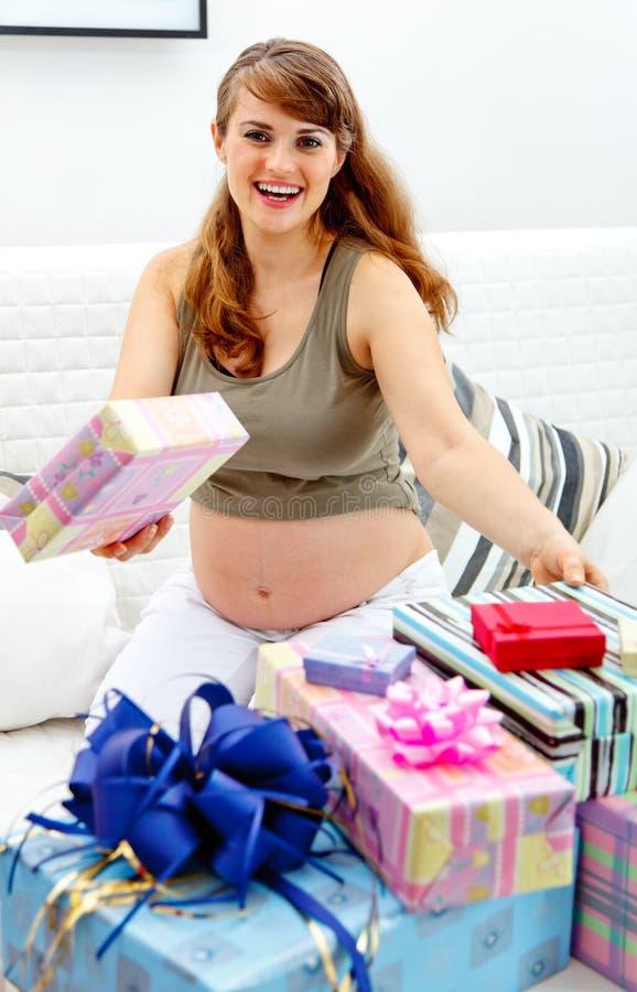 Schwangere Frau mit Geschenken für ihr ungeborenes Schätzchen lizenzfreies stockfoto
