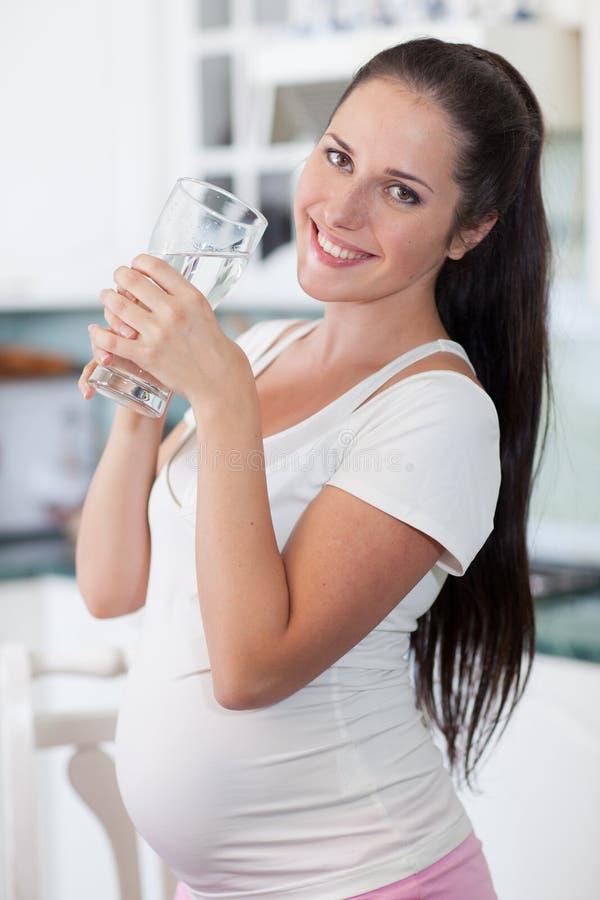 Schwangere Frau mit Glas Wasser. stockfotografie