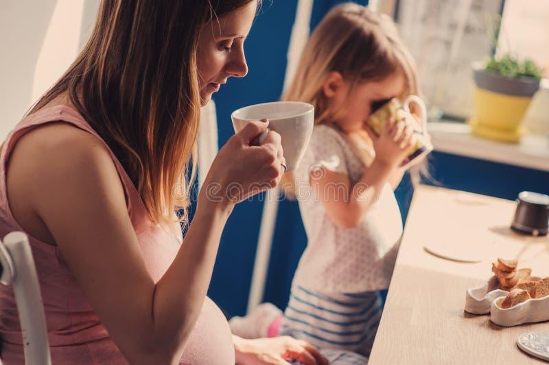 Schwangere Frau mit ihrem trinkenden Tee der Kleinkindtochter zum Frühstück zu Hause