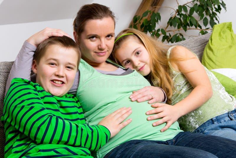 Schwangere Frau mit ihren Kindern lizenzfreie stockfotos