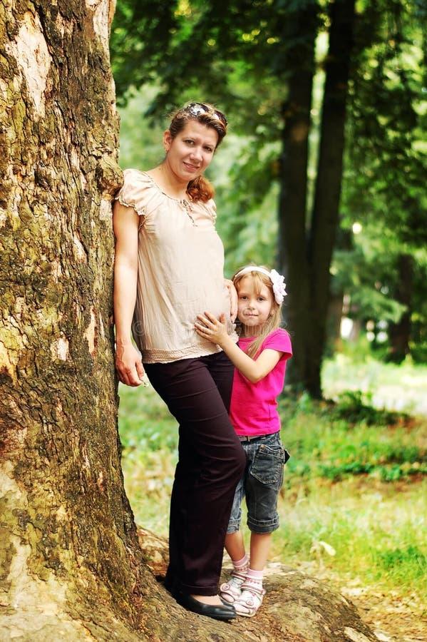 Schwangere Frau mit ihrer Tochter, die in einem Park stillsteht stockbild