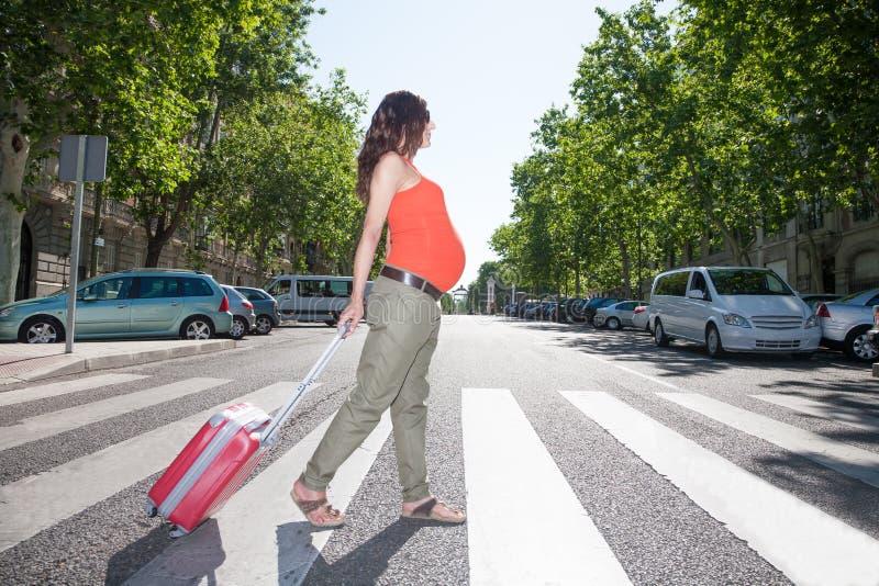 Schwangere Frau mit Koffer im Zebrastreifen lizenzfreies stockbild