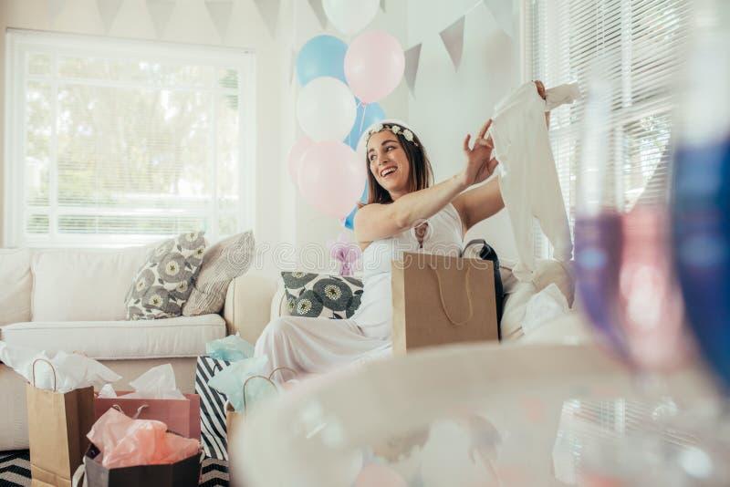 Schwangere Frau mit neuem Geschenk an der Babyparty lizenzfreie stockfotos