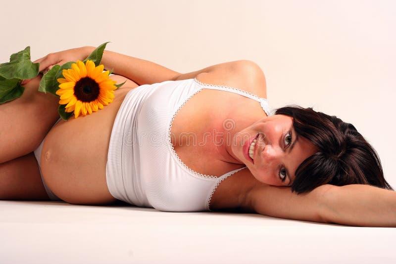 Schwangere Frau mit Sonneblume lizenzfreies stockbild