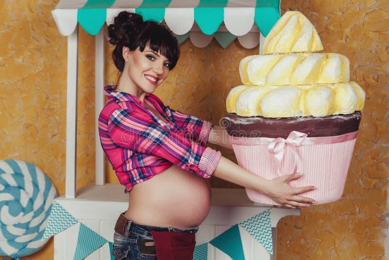 Schwangere Frau mit Spielzeugkuchen lizenzfreie stockfotografie
