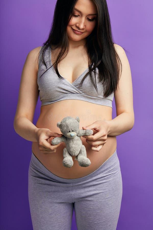 Schwangere Frau mit Spielzeugteddyb?ren junge Frau, die ein Baby erwartet lizenzfreies stockbild