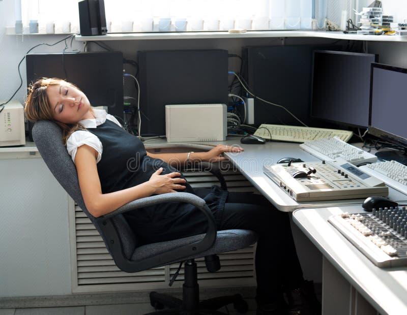 Schwangere Frau schläft bei der Arbeit stockbild