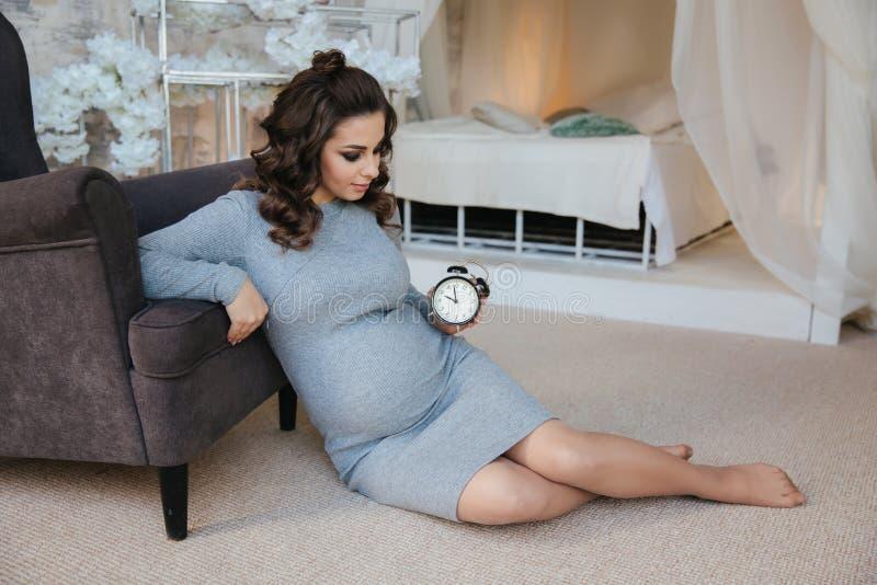 Schwangere Frau sitzen nahe dem Lehnsessel Sch?nheit, die auf ein Baby wartet Elegantes schwangeres Modell zu Hause lizenzfreies stockbild