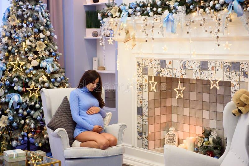 Schwangere Frau sitzt in einem Lehnsessel am Fenster nahe bei Weihnachtsbaum Sie betrachtet durchdacht ihrem Bauch stockfotografie