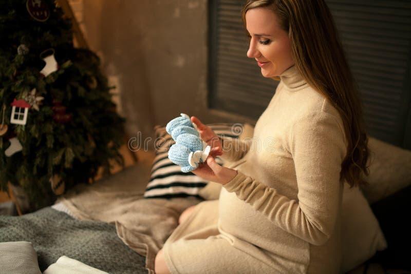 Schwangere Frau sitzt vor Weihnachtsbaum und betrachtet Baby ` s BO stockfotografie