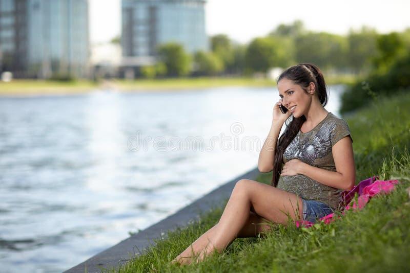 Schwangere Frau spricht durch einen Handy stockfoto