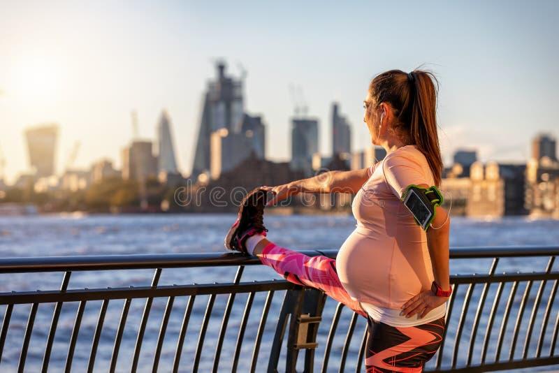 Schwangere Frau tut sie ausdehnend in die Stadt lizenzfreie stockbilder