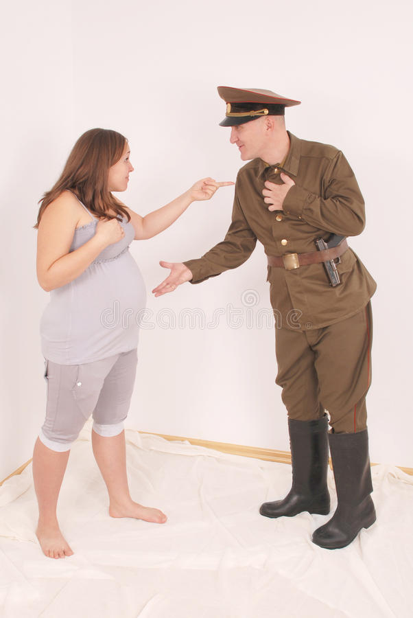 Schwangere Frau und ein Mann in der Uniform lizenzfreie stockbilder
