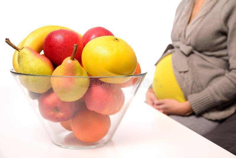 Schwangere Frau und frische Früchte lizenzfreies stockfoto