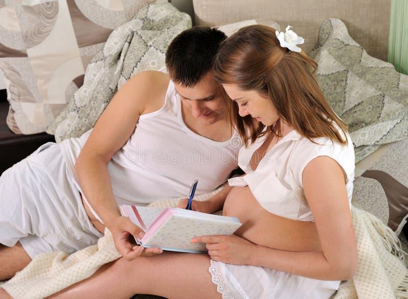 Schwangere Frau und ihr Ehemann, die das Schwangerschaftstagebuch schreibt. lizenzfreies stockbild
