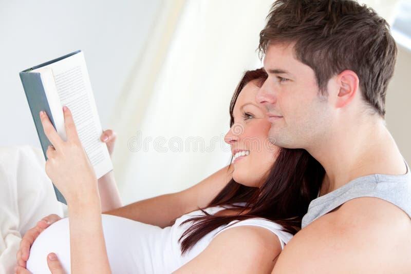 Schwangere Frau und ihr Ehemann, die ein Buch liest stockfoto