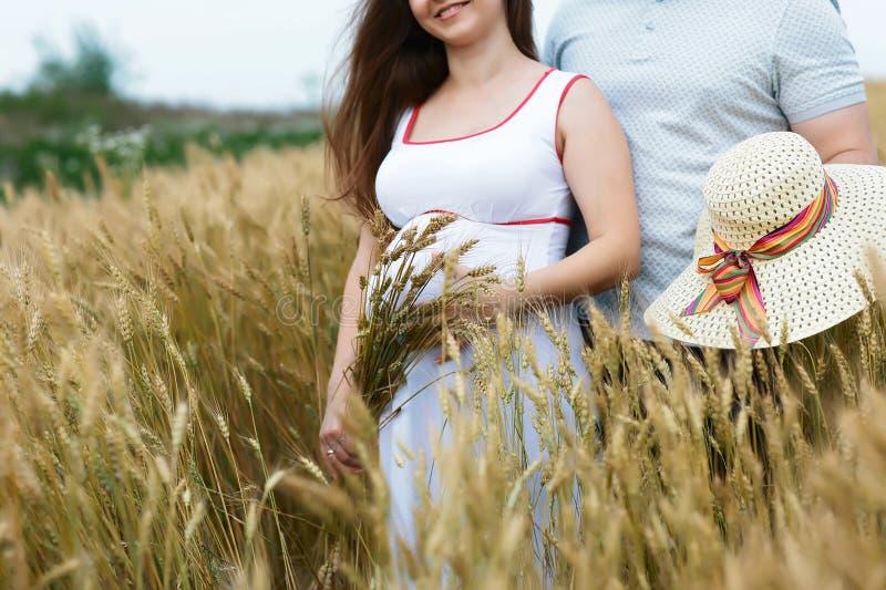 Schwangere Frau und sein Ehemann auf dem Feld mit Ohrringen des Weizens und des Hutes Abschluss oben stockfotografie