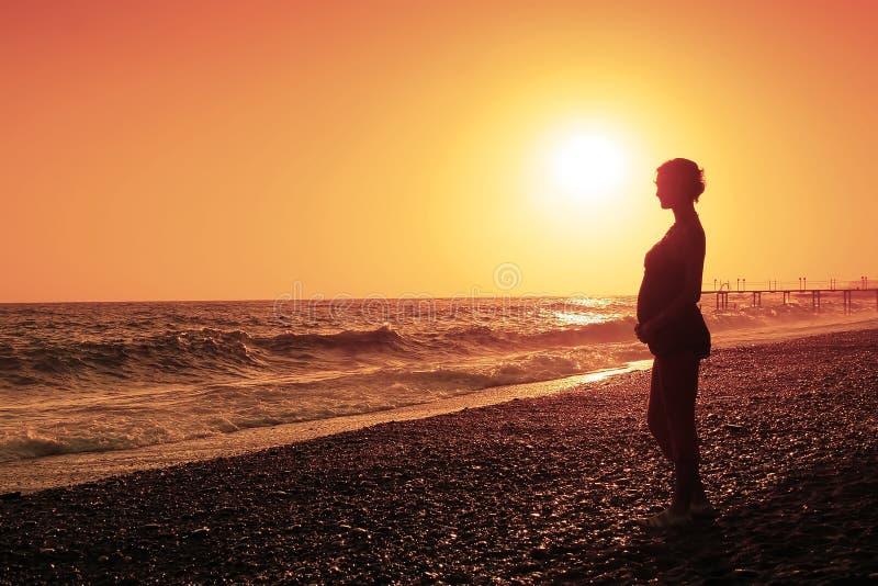 Schwangere Frau und Sonnenuntergang lizenzfreie stockbilder