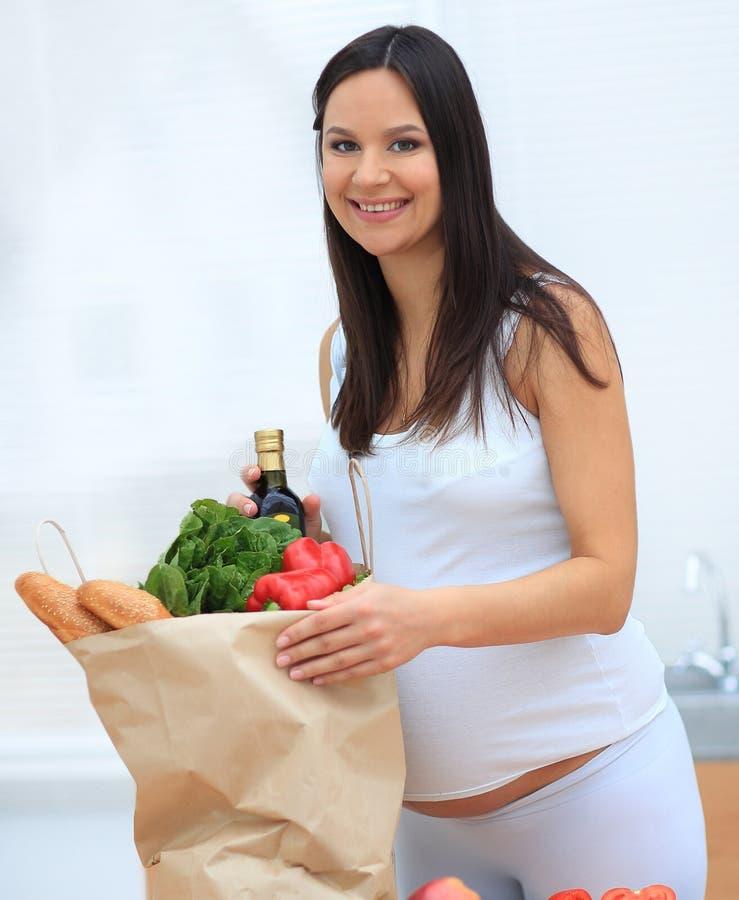 Schwangere Frau, welche die Tasche von Lebensmittelgeschäften, stehend in der Küche hält stockfotografie