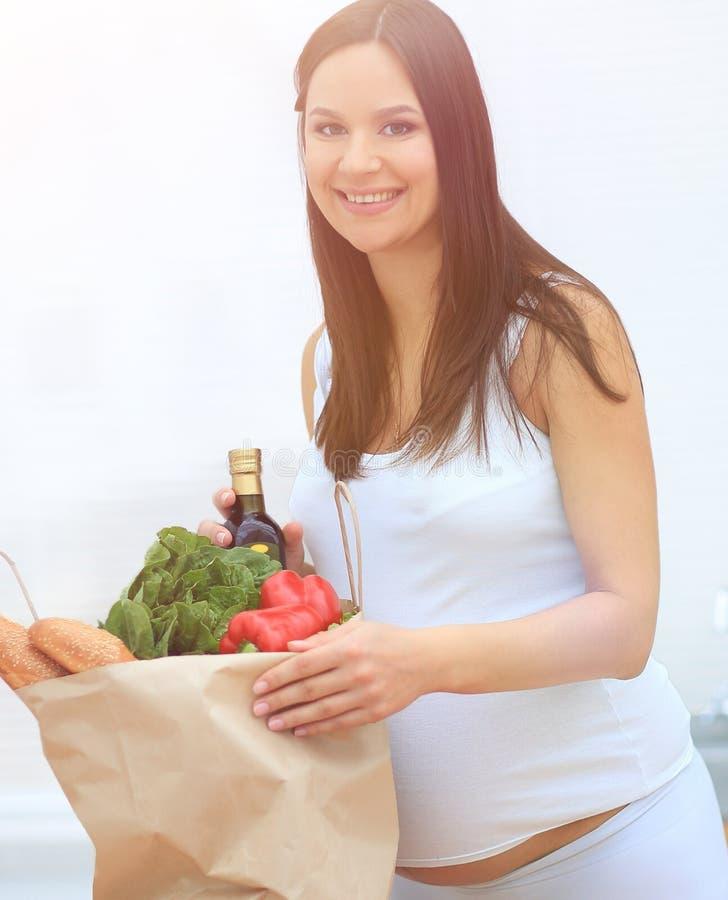 Schwangere Frau, welche die Tasche von Lebensmittelgeschäften, stehend in der Küche hält lizenzfreie stockfotografie