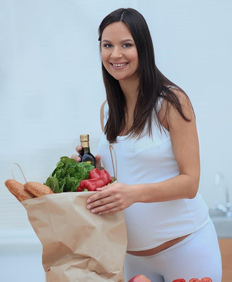 Schwangere Frau, welche die Tasche von Lebensmittelgeschäften, stehend in der Küche hält lizenzfreie stockbilder