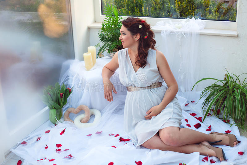 Schwangere Frau zu Hause, die beiseite schaut lizenzfreie stockfotos