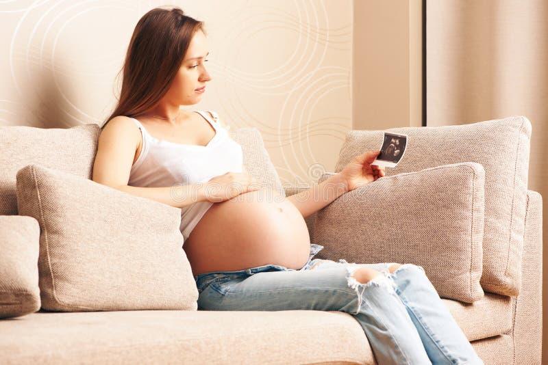 Schwangere Frau zu Hause, die Ultraschallscan hält stockfotografie