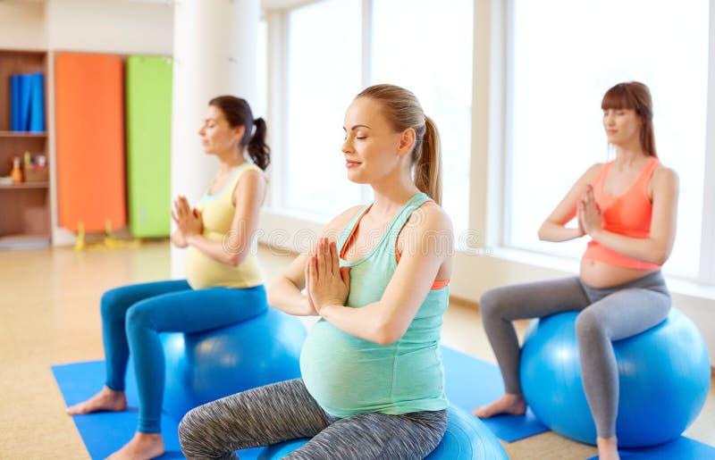 Schwangere Frauen, die auf Übungsbällen in der Turnhalle sitzen stockfotografie