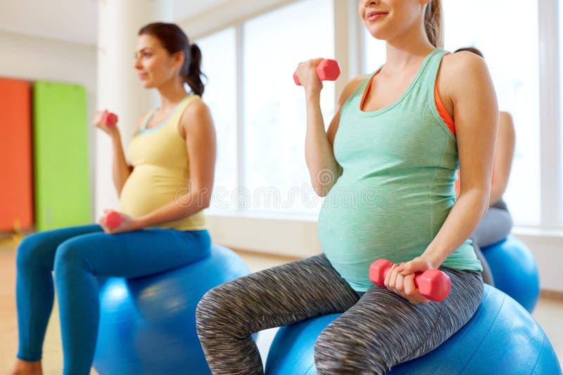 Schwangere Frauen, die mit Übungsbällen in der Turnhalle ausbilden stockfotografie