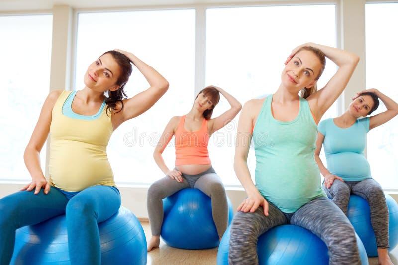 Schwangere Frauen, die mit Übungsbällen in der Turnhalle ausbilden lizenzfreie stockbilder