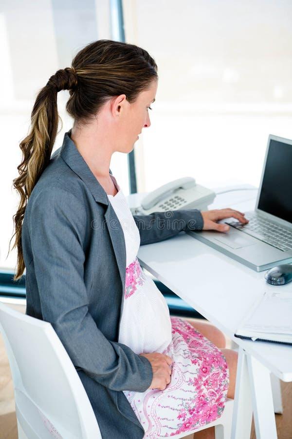 schwangere Geschäftsfrau auf ihrem Laptop lizenzfreie stockfotos