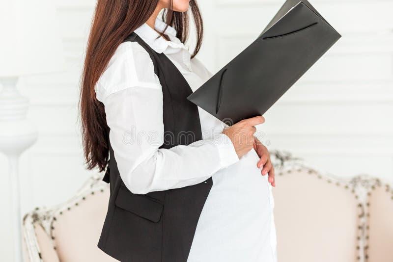 Schwangere Geschäftsfrau bei der Arbeit in einem Büro ein Dokument lesend stockfotografie