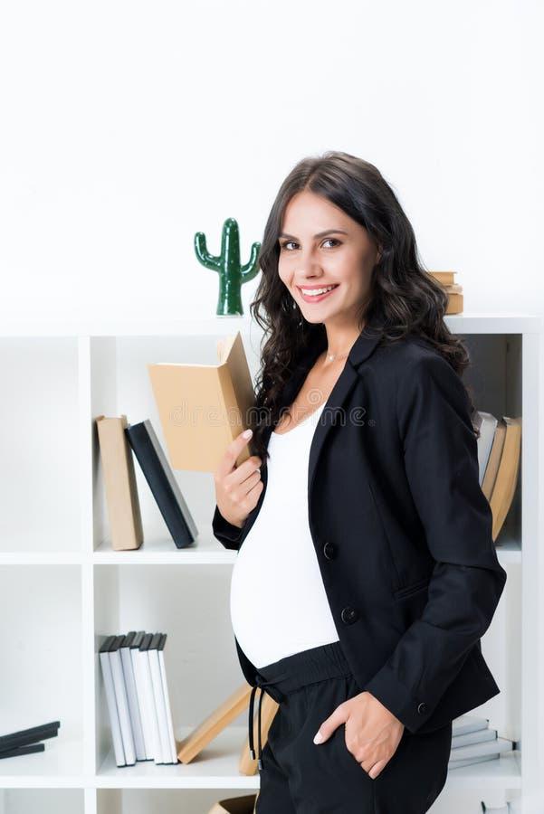 schwangere Geschäftsfrau mit dem Buch, das in der Front steht lizenzfreies stockfoto
