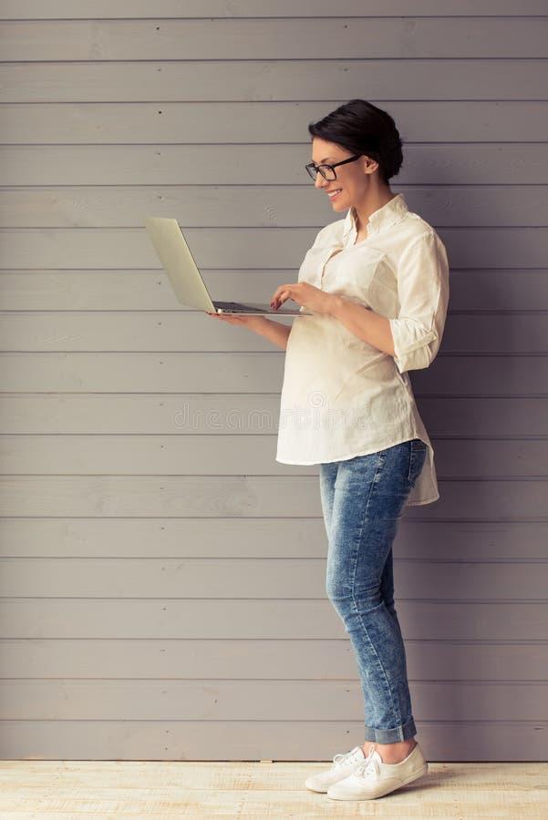 Schwangere Geschäftsfrau mit Gerät lizenzfreies stockbild